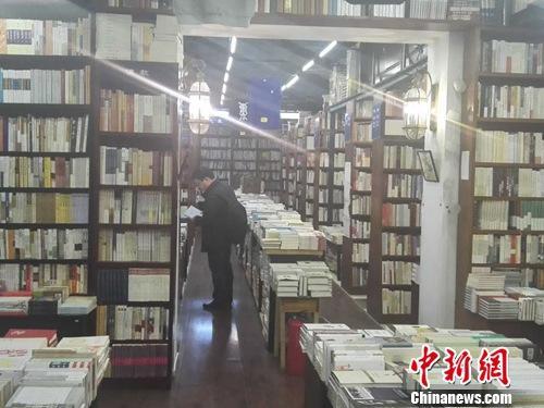 资料图:北京万圣书园店内,读者正在认真选书。