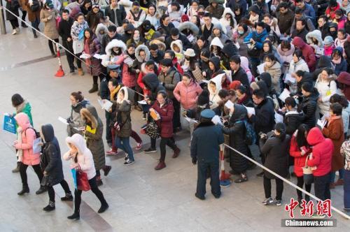 12月10日,山西太原一公务员考点,考生排队准备进入考场。中新社记者 武俊杰 摄