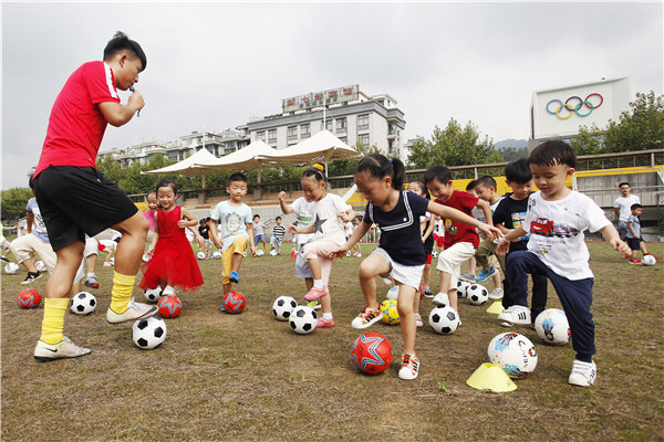 Kindergarten kids in Tonglu county, Zhejiang province enjoy their first soccer lesson under the guidance of a professional coach in September. [Xu Junyong/For China Daily]