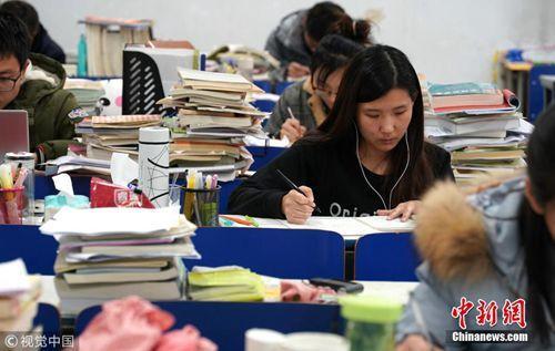 """12月7日,郑州大学新校区,考研进入倒计时,记者探访高校""""考研族""""。图为课桌上,堆满复习资料。马健 摄 图片来源:视觉中国"""