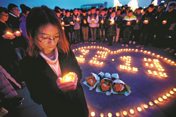 Students from Dongnan University in Nanjing light candles on Tuesday to commemorate the Nanjing Massacre, which began 80 years ago on Wednesday. A memorial hall commemorating the tribunal of accused war criminals in Tokyo will be built in Shanghai. YANG BO / CHINA NEWS SERVICE