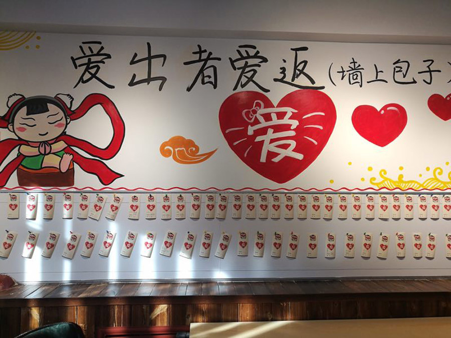 In the restaurant, a wall is filled with cards, on which all the information related to donation is clearly written. [Photo provided to chinadaily.com.cn]