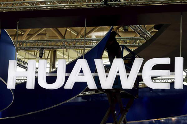A worker adjusts the logo at the stand of Huawei at the CeBIT trade fair in Hanover, March 15, 2015.[Photo/Agencies]