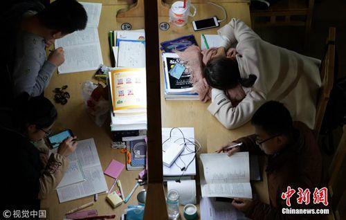 """12月7日,郑州大学新校区,考研进入倒计时,记者探访高校""""考研族""""。图为夜晚的图书馆里,考研学生占了相当大比例。马健 摄 图片来源:视觉中国"""
