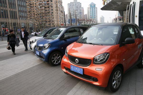 """资料图片:2月16日,在上海曲阜路街头,行人经过路旁的""""共享汽车""""。新华社记者 丁汀 摄"""