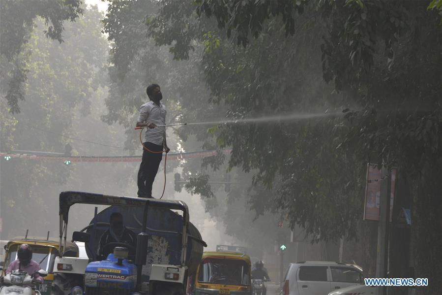 A municipal worker sprays water on the tree to settle dust as a measure against ongoing heavy pollution in the air in New Delhi, India on Nov. 9, 2017.(Xinhua/Sarkar)