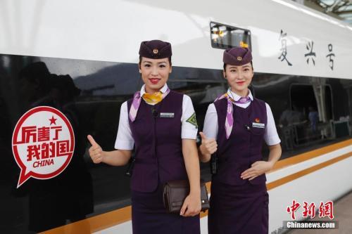 """资料图:京沪高铁""""复兴号""""G2次列车乘务员在车门口等待旅客的到来。"""