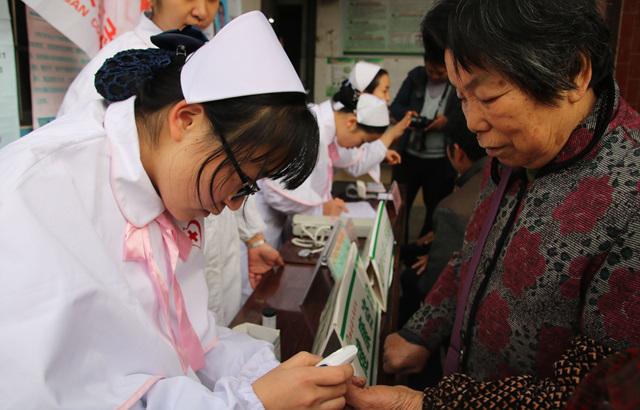 南丁格尔志愿护理服务融安县人民分队志愿者在为群众免费测量血糖.jpg