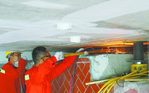 ▲工人在拆除旧的桥梁支座,一旁黄色管道连接的机器为千斤顶。