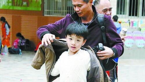 昨日厦门明显降温,图为家长为刚放学的孩子添衣保暖。