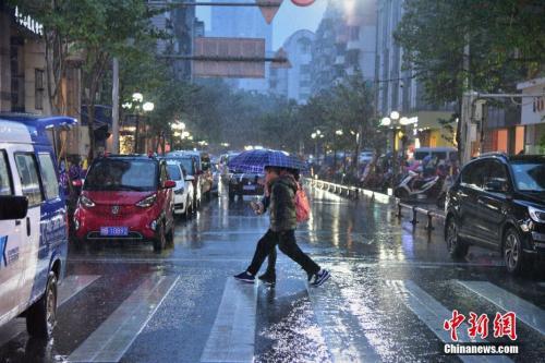 1月6日,广西柳州市遭遇了小寒后的强降雨天气,温度骤降,市民纷纷穿上了大棉衣、撑伞出行。 王以照 摄