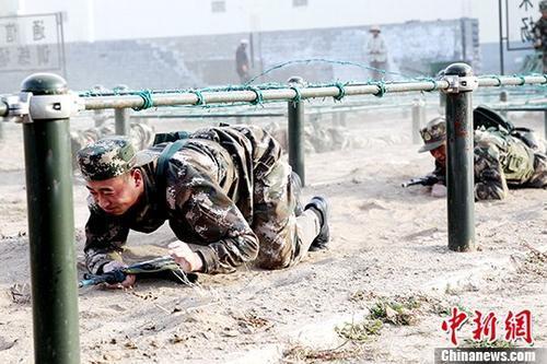 资料图:新兵正在匍匐前进。中新社记者 张添福 摄
