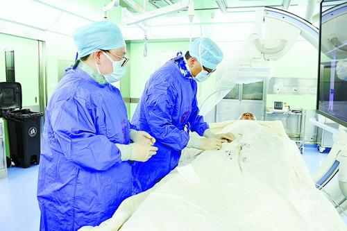 张博恒副院长(右)在DSA手术室为患者进行介入治疗。