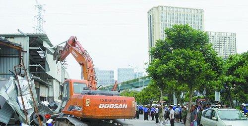 在大型机械的协助下,城管执法人员拆除了一万多平方米的铁皮违建。