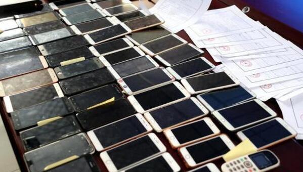 资料图:郑州市公安局文化路分局查获的电脑、手机、存折、银行卡等涉案物品堆满桌。