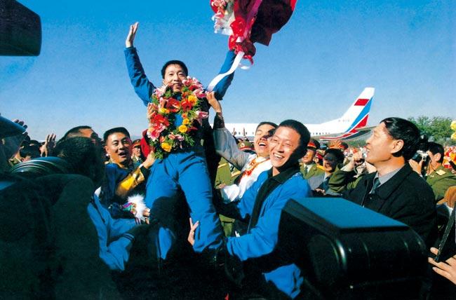 2003年10月16日 执行神舟五号任务航天员杨利伟返回西郊机场被欢呼的人群抛起 摄影:朱九通