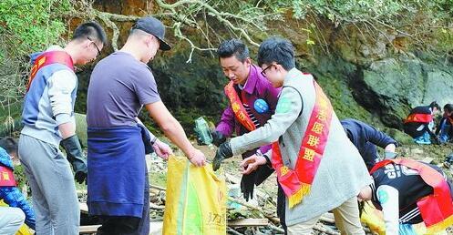 环保志愿者正在海岸线上清理垃圾