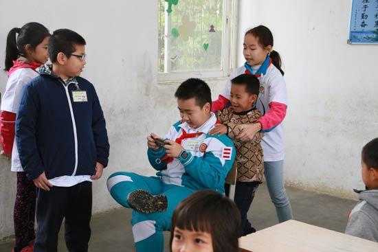 """广东省广州市的小学生到广东清远的山村小学支教,为山村留守儿童上网络安全课。图为""""小讲师""""们演出情景剧模拟孩子们玩游戏时的不良姿势,让学生们纠正。"""