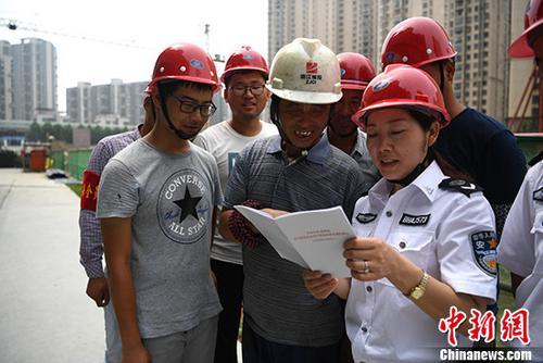 资料图:工作人员给农民工普及安全生产知识。中新社记者 韩苏原 摄