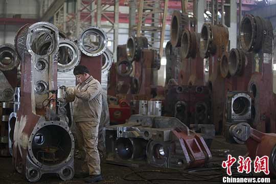 资料图:山西太重工人正在检测机械配件。 中新社记者 张云 摄