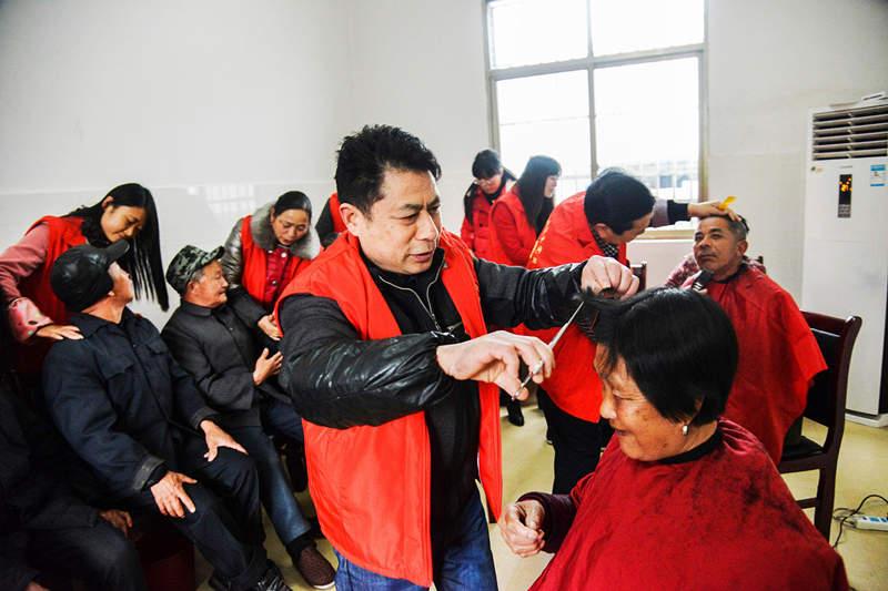 在新余颐养之家,志愿者们正为老人免费理发。