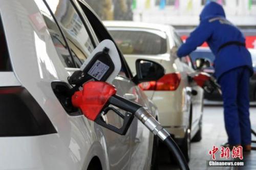 资料图:山西太原,加油站工作人员给汽车加油。中新社发 武俊杰 摄