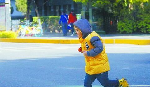 连日来厦门晴天寒冷。图为在街头玩耍的萌娃