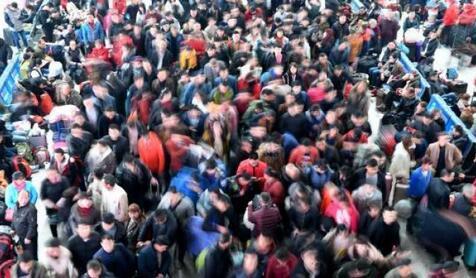 ↑资料图:2月9日,福州火车北站旅客在候车厅排队等候检票上车。