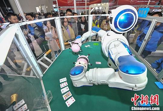 资料图:武汉光博会,可以玩扑克牌的双臂机器人吸引众多参观者。 中新社记者 张畅 摄