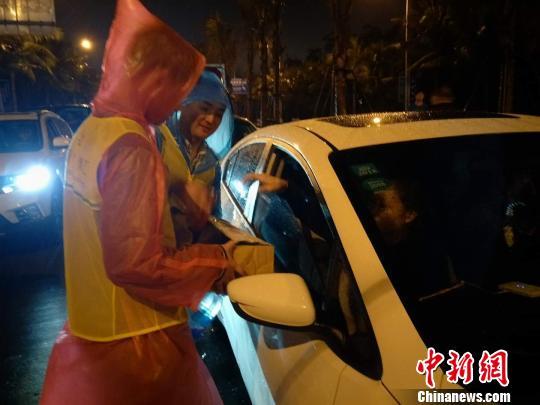 志愿者在雨夜中为滞留旅客服务