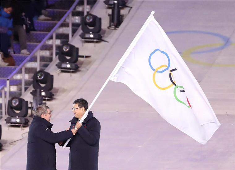 2月25日,北京市市长陈吉宁(右)从国际奥委会主席巴赫手中接过奥林匹克会旗。新华社记者 白雪飞摄