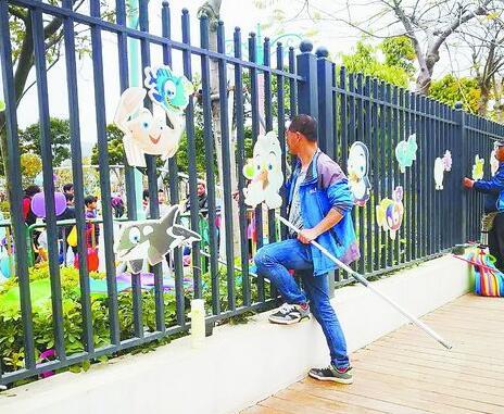 厦门儿童公园围栏外侧,小贩撑着杆子往园内兜售滑板