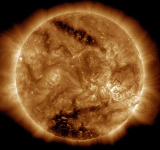 "NASA的太阳观测卫星""太阳动力学天文台""(SDO)捕捉到了太阳表面的两处巨大""黑斑""。这些巨大的黑斑也被称为""冕洞"",是由于太阳表面的磁场粒子,被太阳风吹出太空,导致有部分地区呈现较深的颜色。这是继SDO卫星在1月份拍到太阳南极附近出现巨大黑色区域后,太阳表面再次出现大面积""冕洞""。 图片来源:NASA官网"