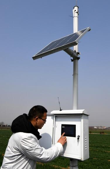 河南省温县农林局植保站的技术人员在查看麦田信息遥感监测仪。