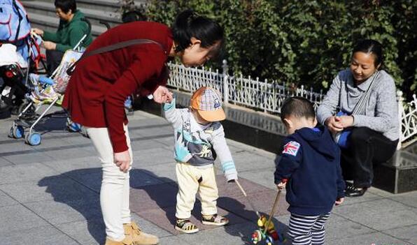 资料图:北京街头两名孩子在母亲的带领下玩耍。