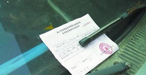 联合整治前,城管执法部门对乱停放的车辆开具责令改正通知书。