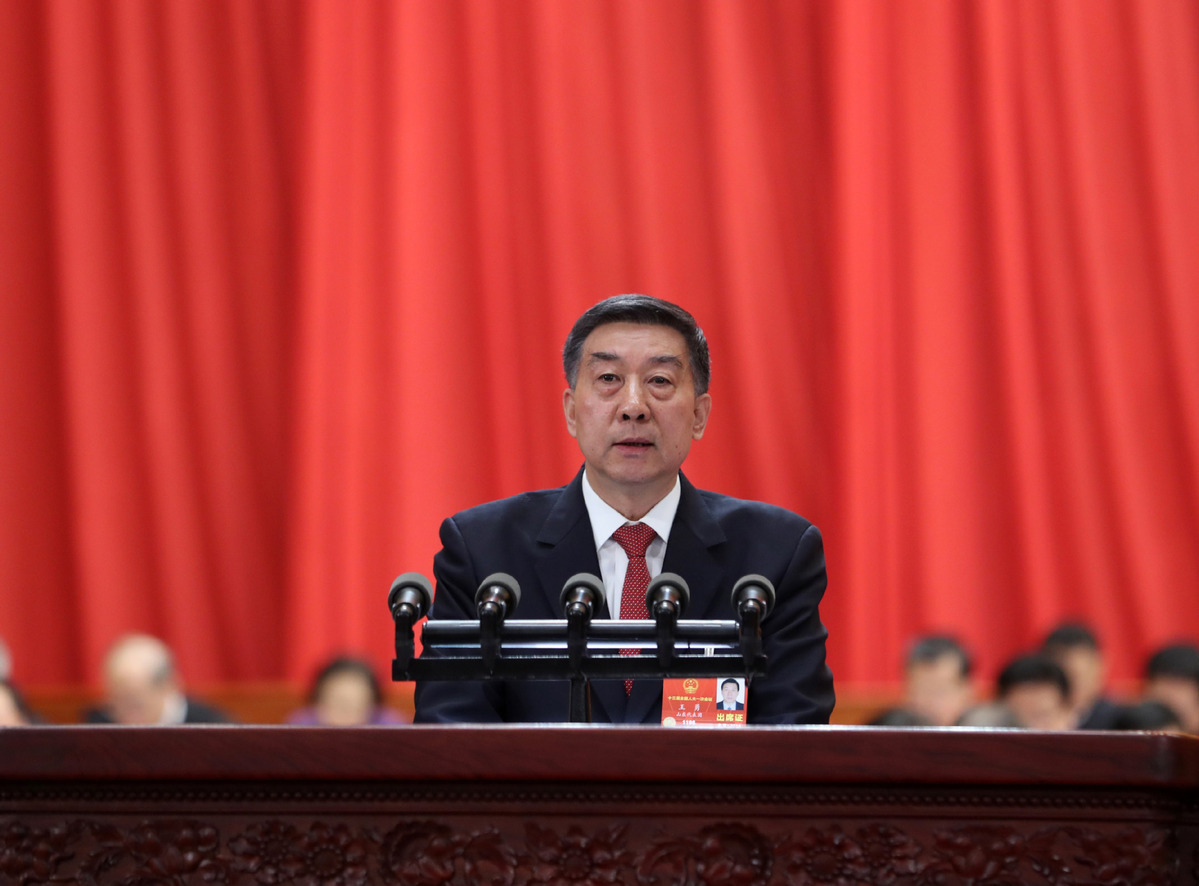 Chinese State Councilor Wang Yong delivers an institutional restructuring plan of the State Council at the fourth plenary meeting of the first session of the 13th National People