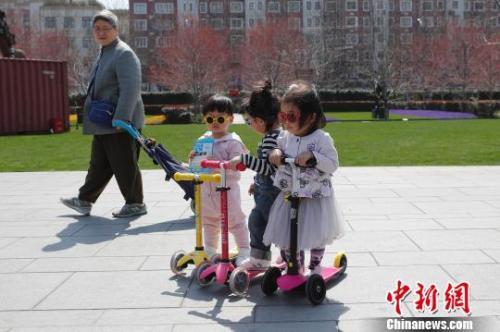 近日,上海气温回升,市民带着孩子在静安雕塑公园享受春意。