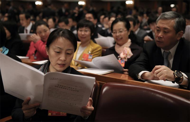 A deputy reads a document at the fourth plenary meeting of the first session of the 13th National People's Congress in Beijing on Tuesday. XU JINGXING / CHINA DAILY
