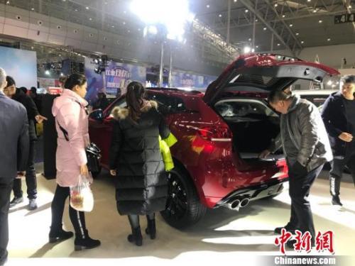 资料图:某车展上,消费者在参观展示的汽车。