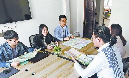 旅行定制师李波(左二)与同事开会讨论定制路线。