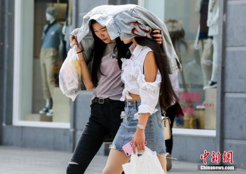 4月3日,武汉江汉路步行街上,两名年轻女性用外套遮挡火辣的阳光。当日,武汉主城区最高气温已达30摄氏度。 中新社记者 张畅 摄
