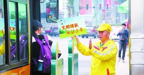 """""""小黄帽""""志愿者引导乘客排队有序上车。"""