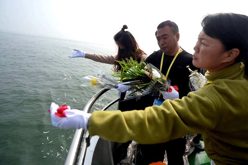 Beijing residents scatter the ashes of relatives into the Bohai Sea from the first boat in China to specialize in sea burials. Wei Tong / For China Daily