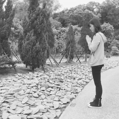 在台北市富德墓园树葬区的一排松柏前,包归雁双手合十,祭拜外公。