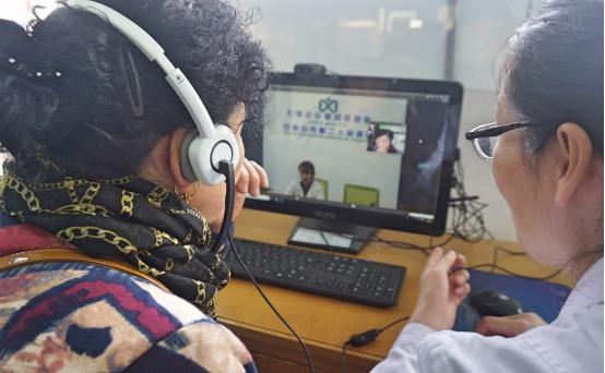 大武口区永乐社区卫生服务中心的社区医生正在帮助患者与上级医生交流病情