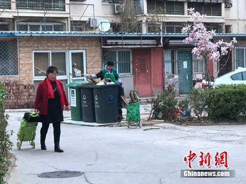 某小区内,垃圾分类志愿者在进行作业。中新网 吴涛 摄