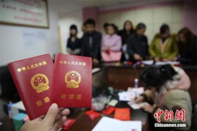 ↑资料图:在四川省内江市东兴区婚姻登记处,新人在展示刚领取的结婚证书。
