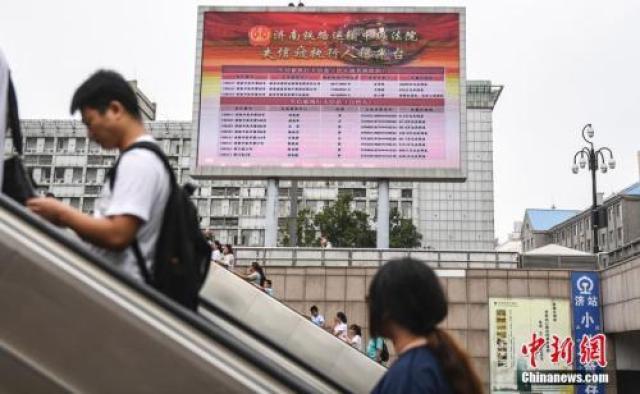 ↑资料图:2017年8月23日,济南火车站广场大屏幕24小时循环播放失信被执行人信息,引得许多旅客驻足观看。
