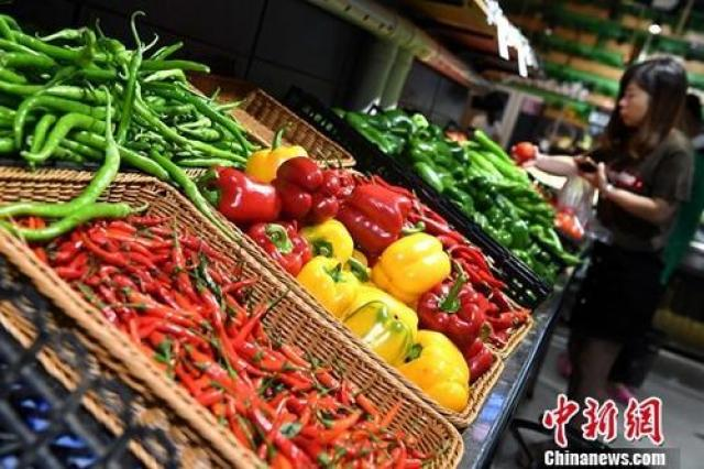 ↑图为市民在超市选购蔬菜。
